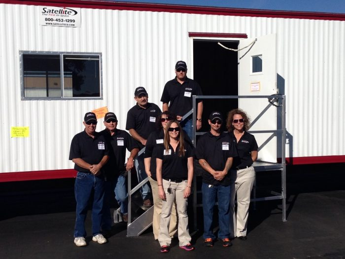 Satellite Shelters branch management team standing in front of mobile office