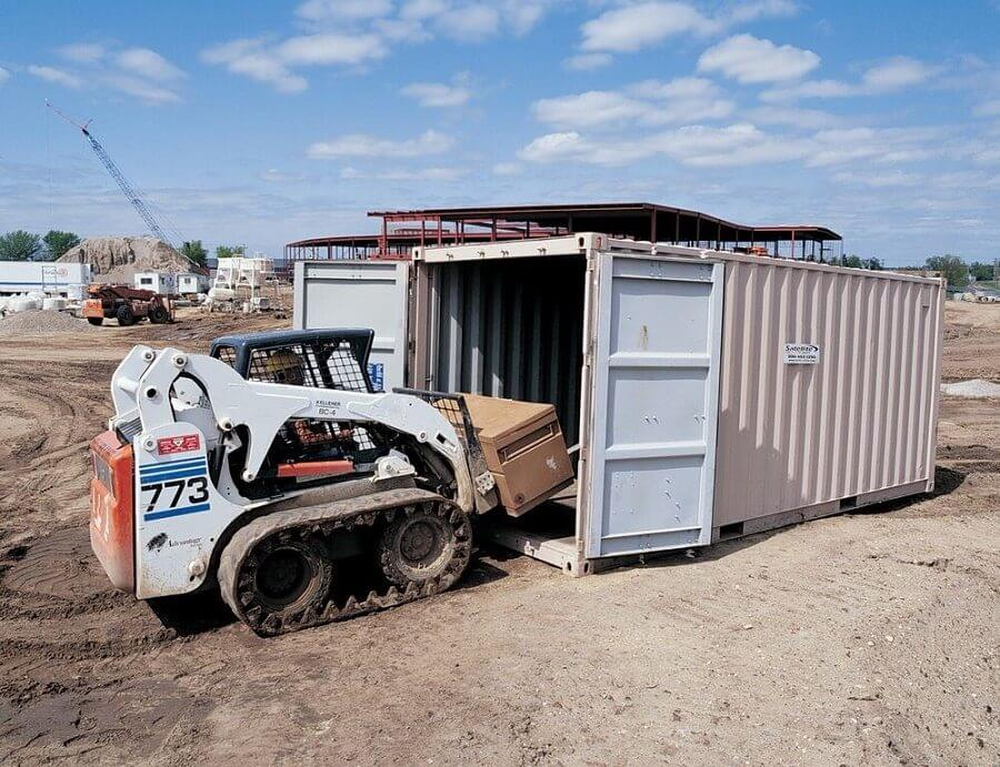 20 foot conex storage container, double doors, small construction vehicle driving inside it