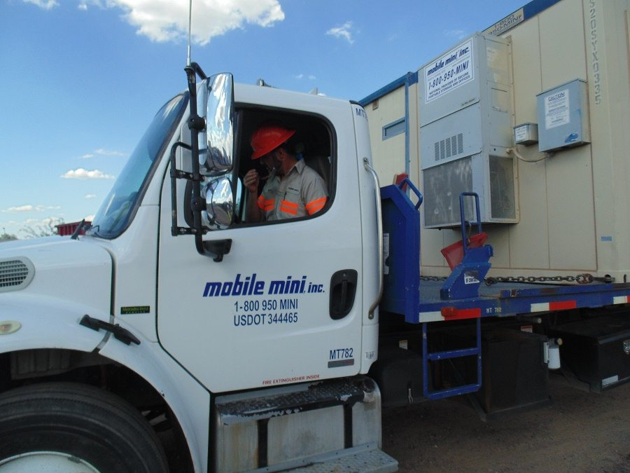 Mobile Mini driver delivering mobile office on flatbed truck and trailer