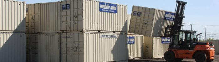 mobile mini storage containers, 40-footers, being stacked in stockyard