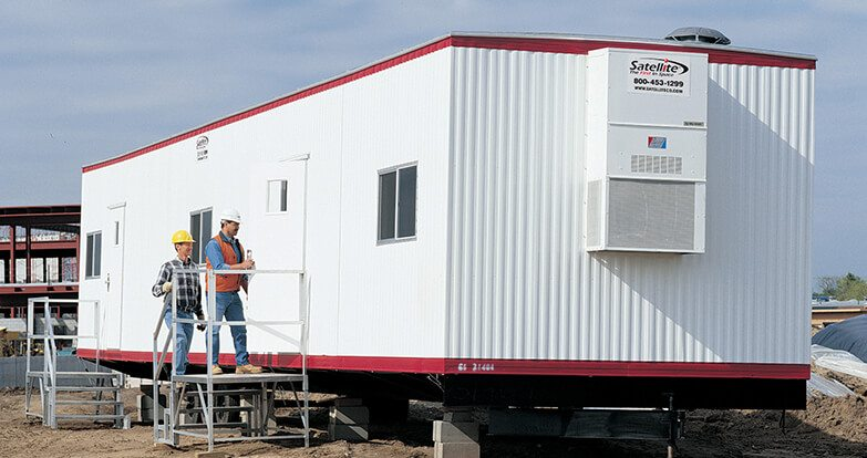 Satellite Shelters mobile office trailer at construction site with workers standing on step ramps