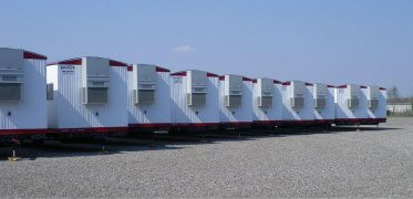 multiple mobile offices on trailer, HVAC units, lined up at Satellite Shelters stockyard