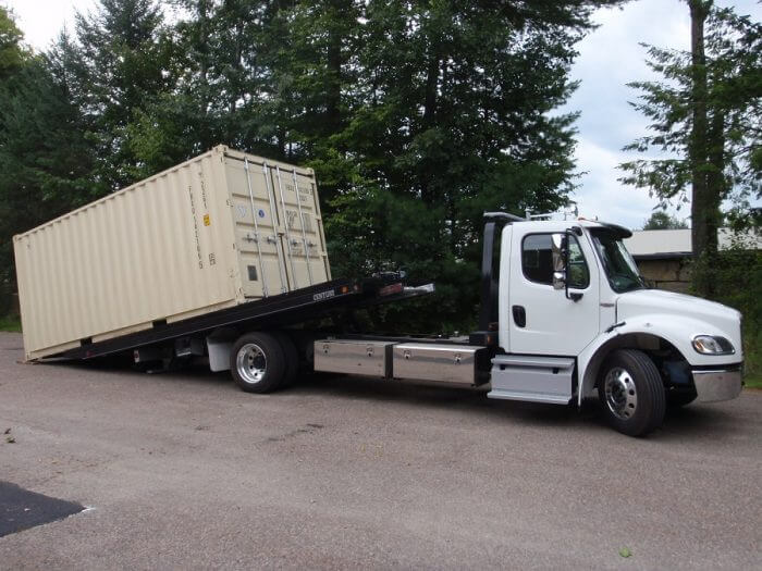 storage container being delivered on a tilt-bed truck and trailer
